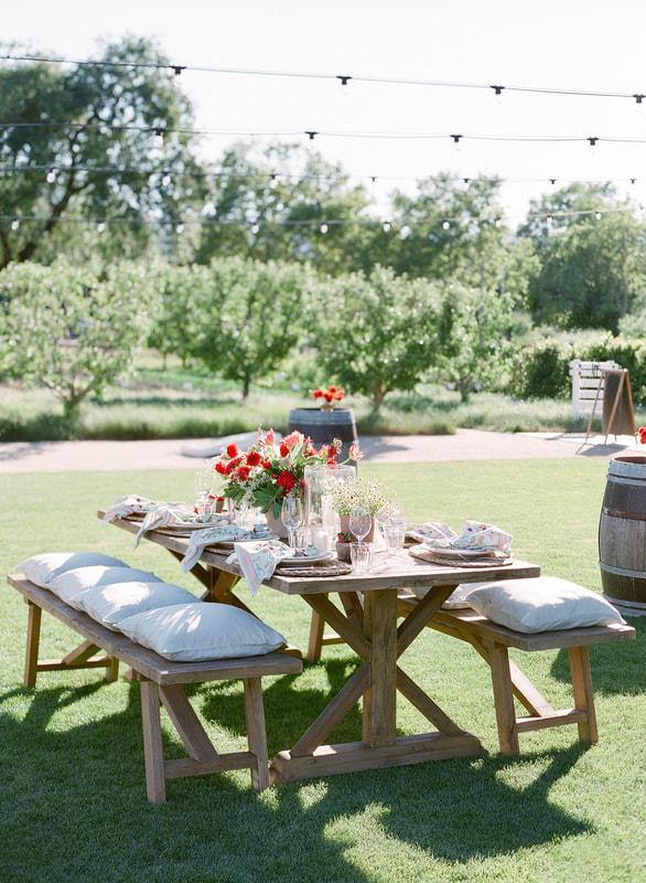 Tables at Rosemary Events welcome party with Mindy Rice Design. Wood Ruskin Tables with Benches and custom pillows.   Photo by Jose Villa