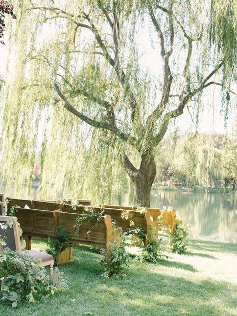 Wedding Pews under a willow tree at Rosemary Events wedding. Floral by Sillapere.   Photo by Kristen Loken